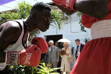 Boxers train as Britain's Prince Charles and Camilla, Duchess of Cornwall, look on during their visit to Jamestown cafe in old British Accra