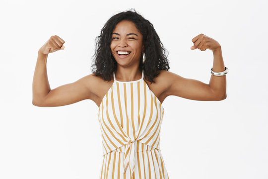 She can deal with any trouble. Portrait of strong and independet joyful stylish african american sportswoman working out in gym standing in trendy overalls and showing muscles winking and smiling