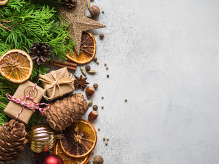 Bright Christmas or New Year background with thuja branches, Christmas decorations, spices, nuts, dried orange slices, pine cones. Copy space.