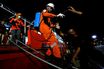 An Indonesian rescue team member carries disinfectant as he disembarks a rescue ship during the recovery process of crashed Lion Air flight JT610 at Tanjung Priok port in Jakarta