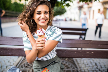 Young latin curly woman sitting on a park bench and eating ice cream in the summer
