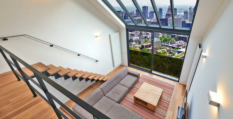 Modern living room with large windows and view on city panorama.