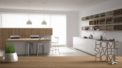 Wooden table, desk or shelf with potted grass plant, house keys and 3D letters making the words home sweet home, over contemporary kitchen, interior design, blur background