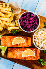 Grilled salmon with french fries and vegetables served on cutting board on wooden table
