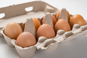 fresh eggs in a paper package close up on white