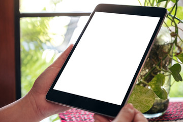 Mockup image of hands holding black tablet pc with blank white desktop screen with green nature background