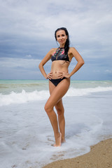 Female person in black bikini posing arms akimbo at the sea