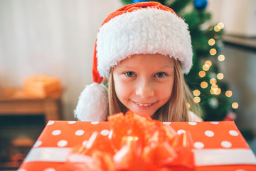 Picture of small and beautiful girl holding read box with present and looks on camera. She is happy. Girl wears Christmas hat on head. There is tree behind her.