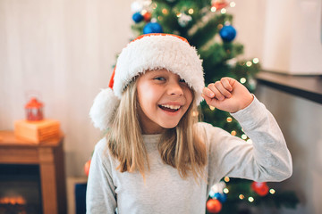 Cheerful and positive girl smiling and laughing. She holds edge of her Christmas hat. Girl stands in room where is decorates Christmas tree.
