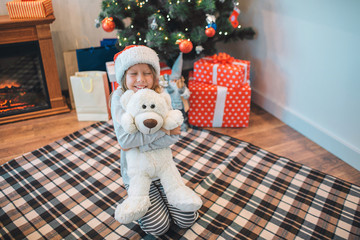 Happy and positive girl sitting on blanket on floor and embacing white toy. She smiles. Girl looks happy. She in room alone.