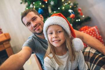 Picture of father and daughter sitting on floor. They look straight and smile. Young man holds camera. They take selfie. Family sitting in decorated room.