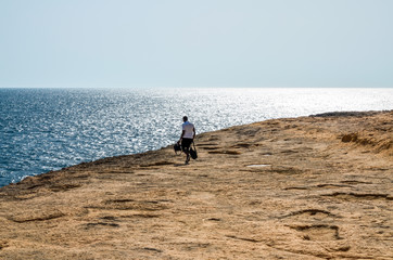 Man walking on a rocky shore by the Mediterranean Sea off the coast of Malta