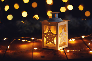 Christmas lantern with lights on a wooden board at night