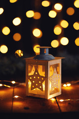 Christmas lantern with lights on a wooden board