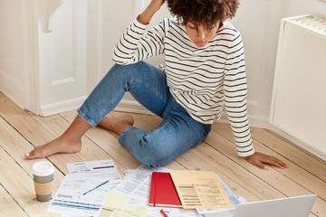 Relaxed freelancer dressed in striped sweater and jeans, works on investment contract, works overtime, uses laptop computer for recieving consultancy, drinks takeaway coffee indoor. Paper work concept