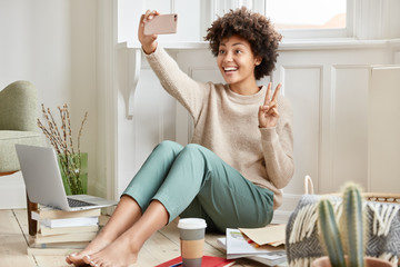 Glad dark skinned female makes video call with cell phone, shows peace sign at camera, greets friend, sits on floor, busy with paper work, uses modern technologies and wireless high speed internet