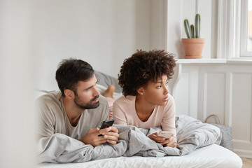 Contemplative family couple use cellulars, concentrated aside, lie in bed at morning, connected to wireless internet at home, text messages, invite friends for party, ignore live communication