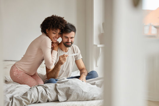 Parenthood, good news, baby expecting concept. Joyful dark skinned wife leans shoulder of her husband, look positively at pregnancy test, going to have child. Family couple on bed in modern apartment