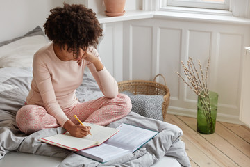 Top view of busy dark skinned woman writes down records in notebook from book, has serious expression, poses on bed, enjoys comfort in bedroom, prepares for examination at college or university