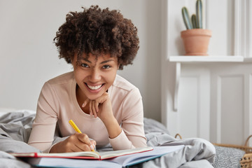 Photo of cheerful young Afro American lady writes down information in notebook with pen, records plans and notes checklist, lies at bed, holds hand under chin, spends weekend at home in bedroom