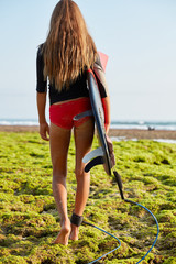 Vertical shot of sporty slim young female dressed in wetsuit, stands back to camera, carries surfboard under arm, has leash around ankle, practises surfing on big ocean waves, admires nature.