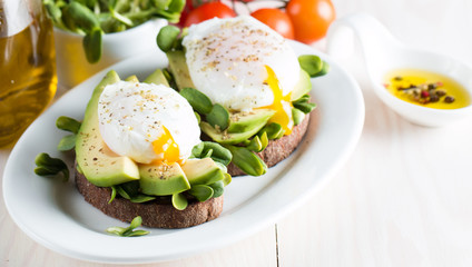 Avocado toast, cherry tomato on wooden background. Breakfast with toast avocado, vegetarian food, healthy diet concept. Healthy sandwich with avocado and poached eggs.