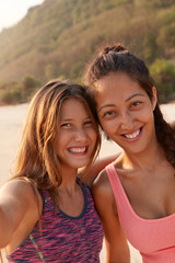 Smiling mixed race female friends pose near for making selfie, dressed in top, have leisure time for sport, model against cliff background, enjoy summer holidays. Friendship, relationships concept