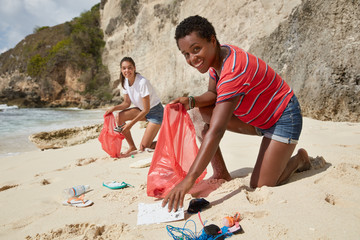 Environmentally friendly multiethnic women pick up plastic and rubber products on seashore, solve global problem, collect waste, care of nature, pose agaist cliff background. Coastal pollution