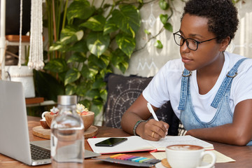 Horizontal shot of pretty dark skinned worker sits at laptop device, learns information from video, writes down in notebook, poses against cozy room interior, drinks tasty latte, has piercing in nose