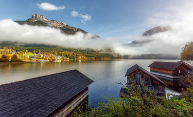 View on Altaussee village with Loser peak in clouds, on background. Wooden Fishing Huts on the foreground. instagram creative image. Dead Mountains (Totes Gebirge). Austrian Alps.
