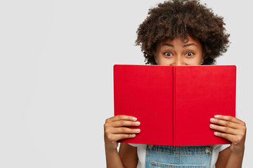 Indoor shot of of cheerful woman covers face with red textbook, has joyful expression, being in high spirit as reads her favourite story, likes fiction, spends leisure with hobby, isolated on white