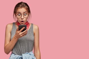 Fototapeta Photo of astonished teenage girl stares at screen of smart phone, recieves unexpected notification, dressed in grey casual vest, poses against pink studio wall with free space aside for promotion obraz