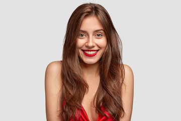 Close up shot of beautiful lady with charming smile, shows natural beauty, has long dark hair, poses bare shoulders against white background, wears red lipstick, expresses happiness. Lifestyle concept
