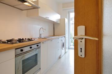porte ouvrant sur petite cuisine d'appartement