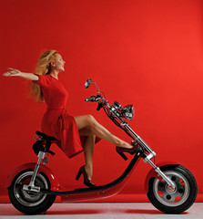 Woman ride new electric car motorcycle bicycle scooter with hands spread freedom sign laughing smiling on red background