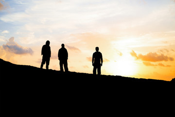 Group of three men silhouetted against a sunset sky
