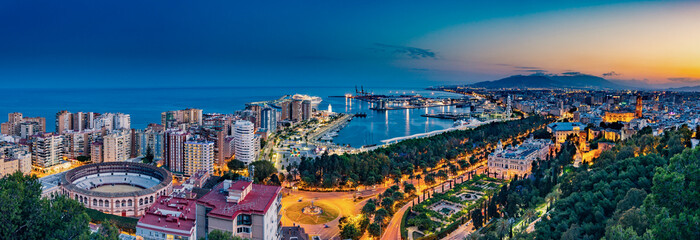 Night aerial panorama of Malaga, Spain with skyscrapers, streets, port, city hall and park during golden hour Fototapete
