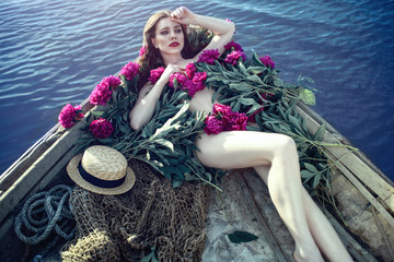 Beautiful woman with perfect body shape lying in the wooden boat covered with peonies. Fishing net and straw hat on the bottom next to her. Deep blue water around.