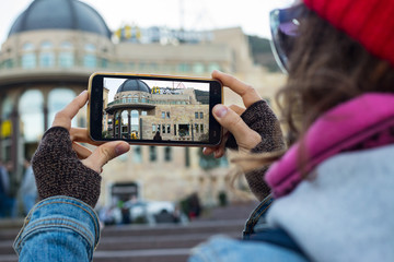 Tbilisi, Georgia - October 30 2018: white tourist hipster young woman in red hat make smartphone photo of Mcdonalds restaurant at Rustaveli metro station for blogging. Fast food chain, tourism, travel