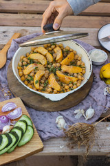 Woman hands open lid of baked chickpea with quince in cast iron skillet, frying pan. Vegan vegetarian lunch, paleo diet, healthy dinner served with salad and vegetables on table