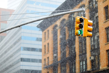 New York city traffic lights with skyscrapers on background during massive snowfall