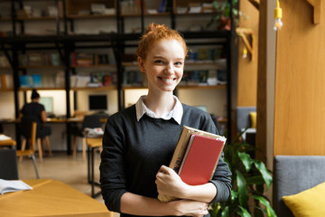 Happy redhead lady student posing indoors in library holding books.
