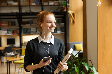 Redhead lady student posing indoors in library holding books listening music with earphones using mobile phone.