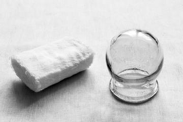 Medical equipment. Retro. Gauze bandage and glass medical jar on a white fabric background. Black and white photo.