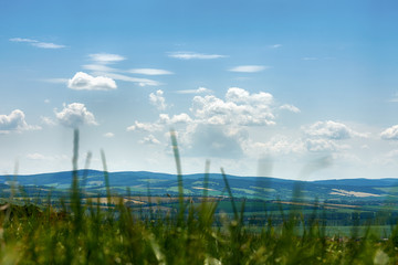 A view of the hillside near Saint Anthony on the farmland around the town of Blatnice in South Moravia. Under a blue sky with clouds