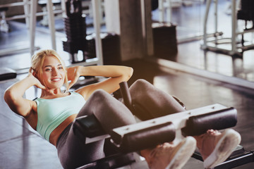 Caucasian women wearing blue tightening exercises are Play abdominal muscles. With a relaxed feel in the gym, which is a set to help keep the body healthy. concept health care and Fitness