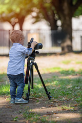 Little boy photographing on the camera on tripod in the park