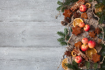 Christmas wooden background with the decor of fir branches, bark, red apples, cookies, cinnamon, anise