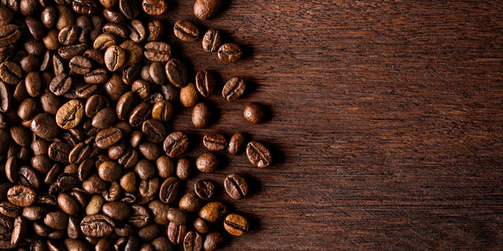 fresh roasted coffee beans on natural dark oak wood panorama wide wooden closeup macro background