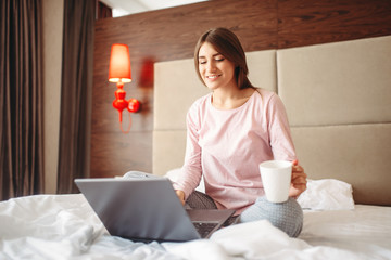 Female person drinks coffee and uses laptop in bed